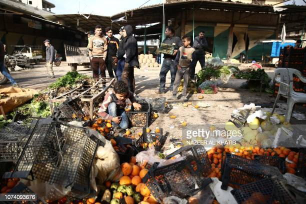 People walk amid scattered vegetables after a car bomb reportedly exploded near a position of proTurkey fighters in a market in the northern Syrian...