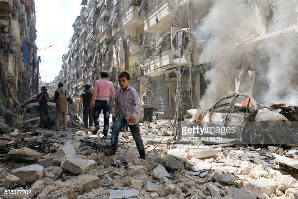 TOPSHOT People walk amid the rubble of destroyed buildings following a reported air strike on the rebelheld neighbourhood of alKalasa in the northern...