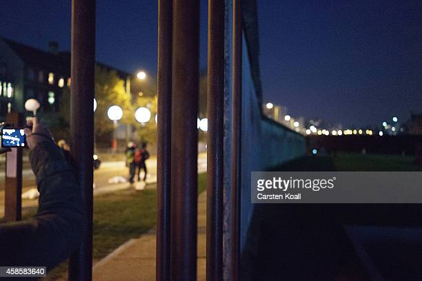 People walk among a light installation of balloons tethered to lamps illuminating the course of the Berlin Wall along the Bernauer Strasse two days...