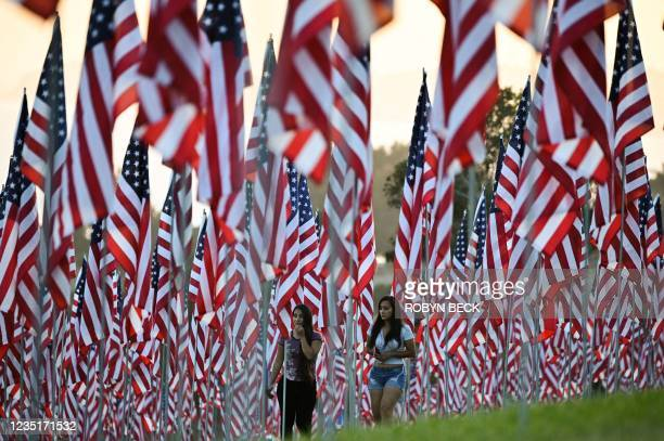 People walk among American flags displayed to commemorate lives lost in the 9/11 terror attack, on September 10, 2021 at Pepperdine University in...