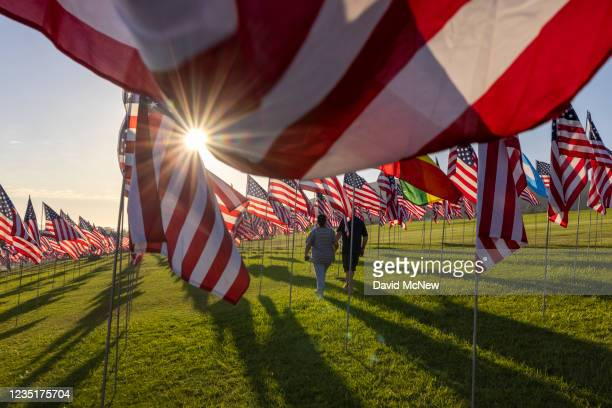 People walk among flags during the 14th annual Waves of Flags on the eve of the 20th anniversary of the September 11 terror attacks in Alumni Park at...