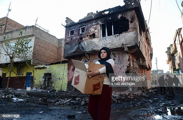 People walk among rubble and damaged buildings in the Sur district in Diyarbakir on December 11, 2015. A policeman was killed on December 9, 2015 by...
