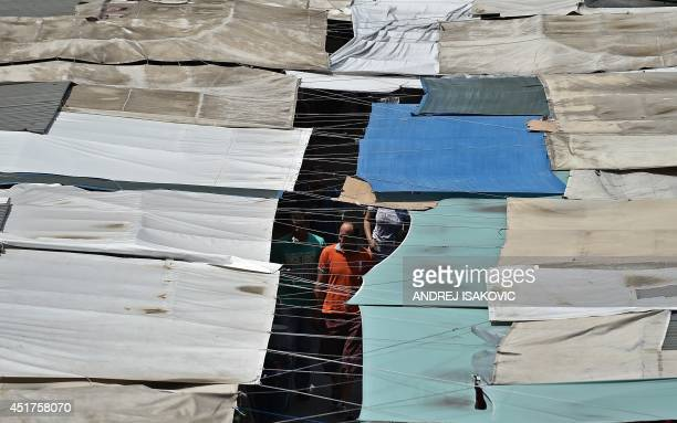 People walk among sstalls where vendors offer diverse goods at the biggest open air market in Belgrade on July 6 2014 With one in five people...