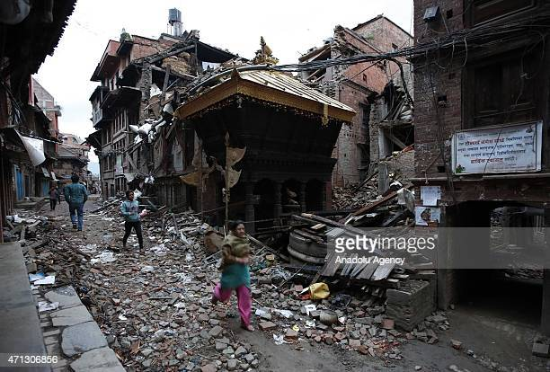 People walk among the debris of houses after a powerful earthquake hits Bhaktapur, Nepal on April 27, 2015. The death toll in Nepal following the...