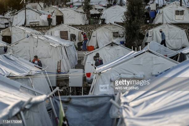 People walk among the tents at an unofficial camp outside the refugee camp of Moria on the Greek island of Lesbos on March 19 2019 When thousands of...