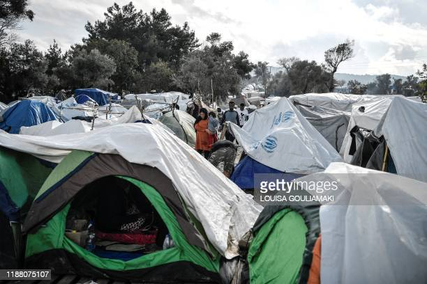 TOPSHOT People walk among the tents in the Vial refugee camp on the Greek island of Chios on December 11 2019 The Vial camp on the island of Chios...
