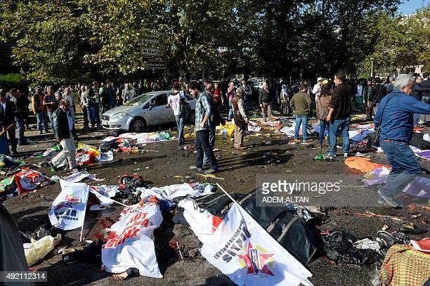 People walk amongs the bodies of people killed in a blast at a peace rally in Ankara on October 10 2015 At least 30 people were feared dead in twin...