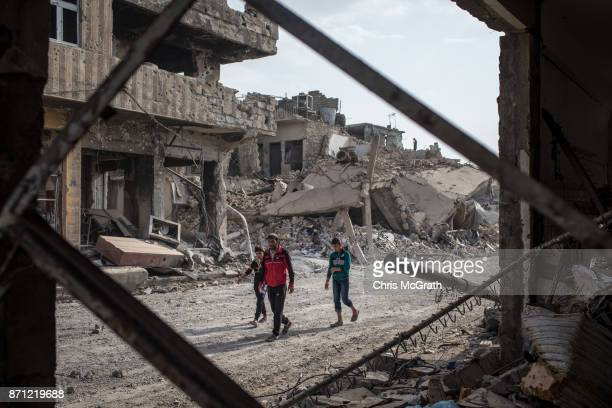 People walk amongst rubble from destroyed buildings in an outer neighborhood of the Old City in West Mosul on November 6 2017 in Mosul Iraq Five...