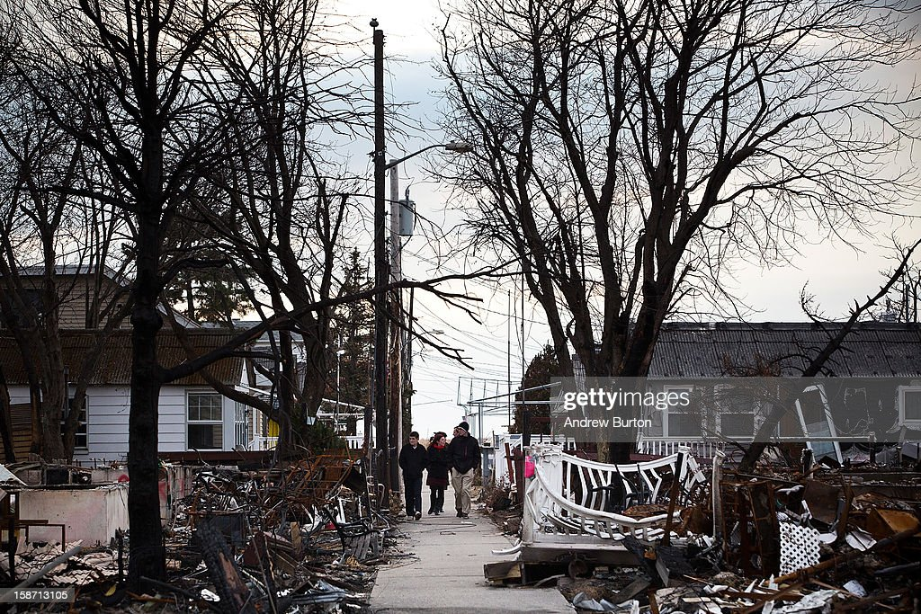 People walk amongst the remains of burned houses in the Breezy Point neighborhood of the Borough of Queens on December 25, 2012 in New York City.