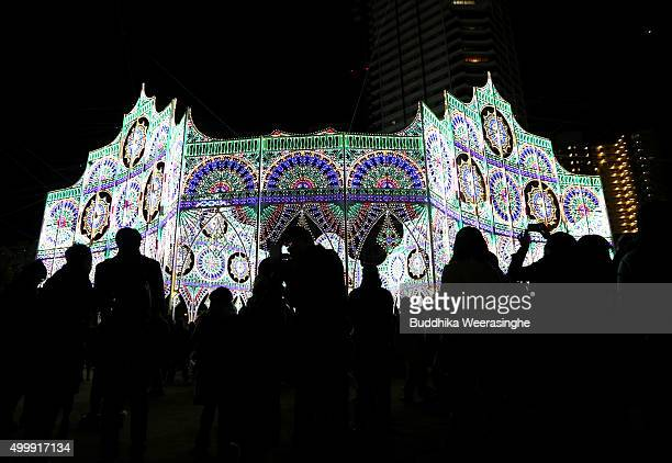 People walk an illuminated structure as a part of the 21th Kobe Luminarie on December 4 2015 in Kobe Japan This annual event initially started in...