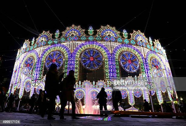 People walk an illuminated structure surrounding a fountain as a part of the 21th Kobe Luminarie on December 4 2015 in Kobe Japan This annual event...