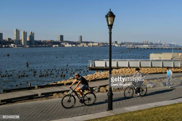 People walk and bike on an unseasonably warm afternoon along the Hudson River February 21 2018 in New York City New York City saw temperatures...