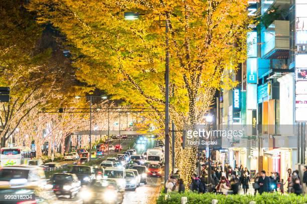 people walk and cars go through rows of illuminated autumn leaves trees at omotesando street for winter holydays season in the night at jingumae, shibuya tokyo japan on december 05 2017. - 表参道 ストックフォトと画像