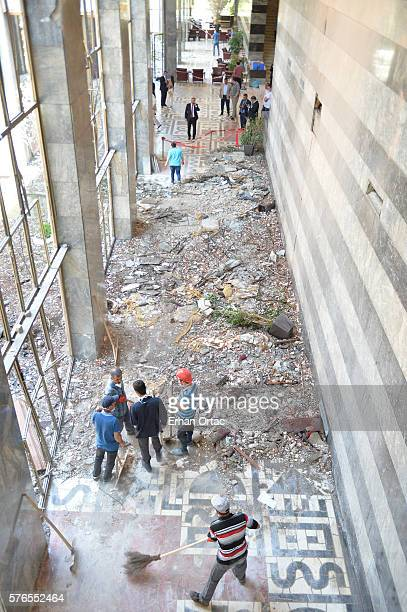 People walk and clean up around the damage and debris at the Turkish parliament which was attacked at least three times through the night during a...