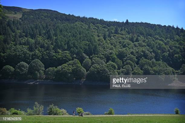 People walk and cycle along the banks of Ladybower Reservoir near Bamford in the Peak District National Park in northern England on May 30, 2020 as...