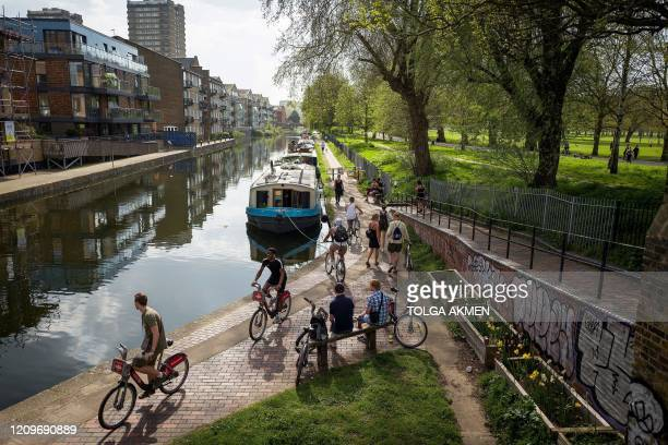 People walk and cycle to take their daily excercise on the towpath alongside the Hertford Union Canal in east London on April 11 2020 as warm weather...