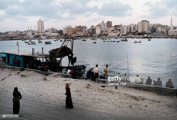 People walk and fish at the port on May 12 2018 in Gaza City Gaza Tensions are high along the GazaIsrael border following more than a month of weekly...