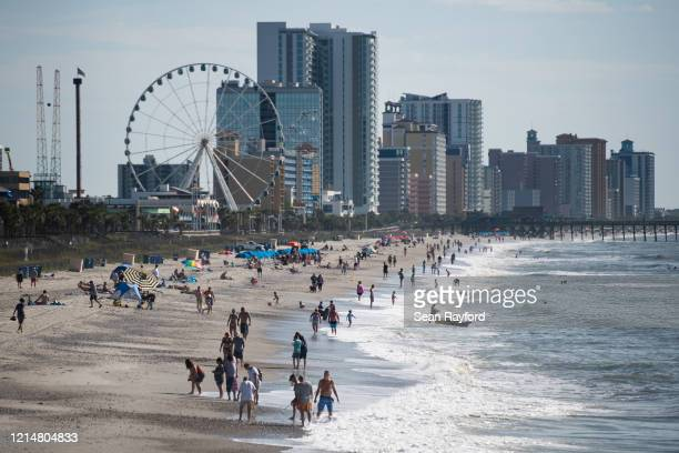 People walk and gather along the beach on the morning of May 23 2020 in Myrtle Beach South Carolina Businesses including amusements have reopened for...
