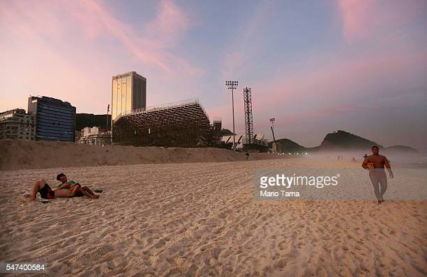 People walk and gather on the beach as preparations at the Olympics site for beach volleyball continue on Copacabana beach on July 14 2016 in Rio de...