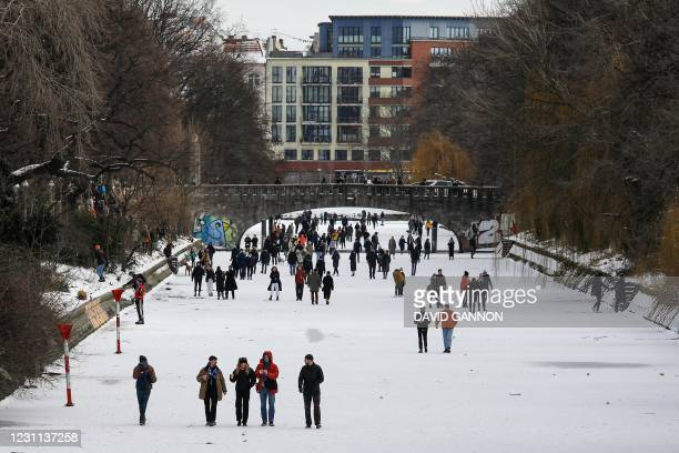 People walk and ice-skate on the frozen Landwehr Canal in Berlin's Kreuzberg district on February 13, 2021 as hundreds of people ignored the warnings...