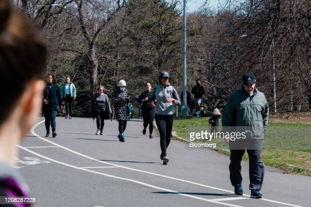 People walk and jog through Prospect Park in the Brooklyn borough of New York, U.S., on Thursday, March 26, 2020. New York Governor Andrew Cuomo said...