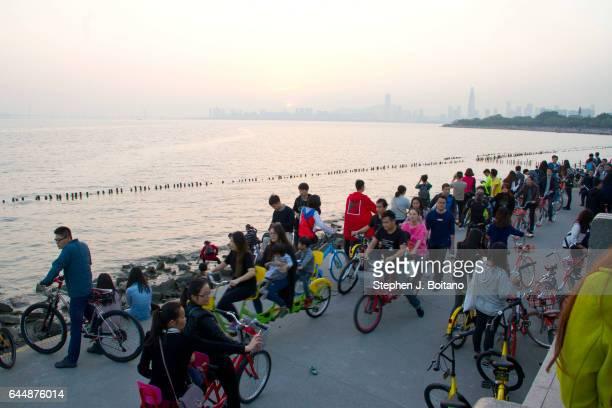 People walk and ride bicycles at a waterfront park on Shenzhen Bay in Shenzhen China