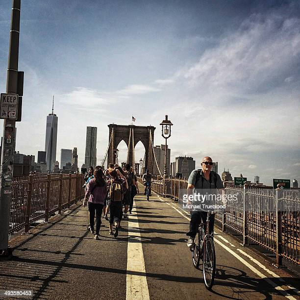CONTENT] People walk and ride bikes across the Brooklyn Bridge with the Freedom Tower in the background