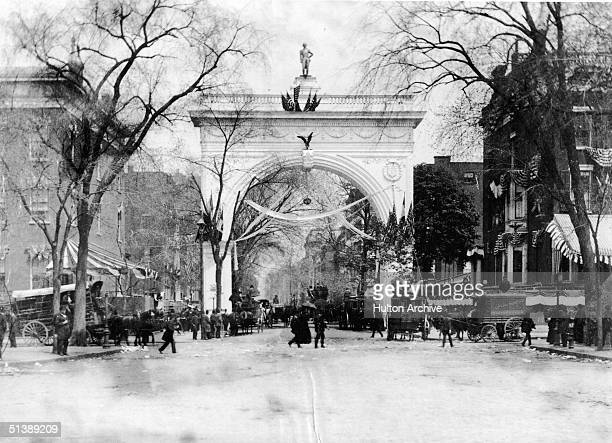 People walk and ride carriages near the arch, covered in papier-mache wreaths, garlands of flowers, and American flags, in Washington Square Park...