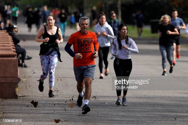 People walk and run to take their daily exercise allowance in Battersea Park in London on March 28 as life in Britain continues during the nationwide...
