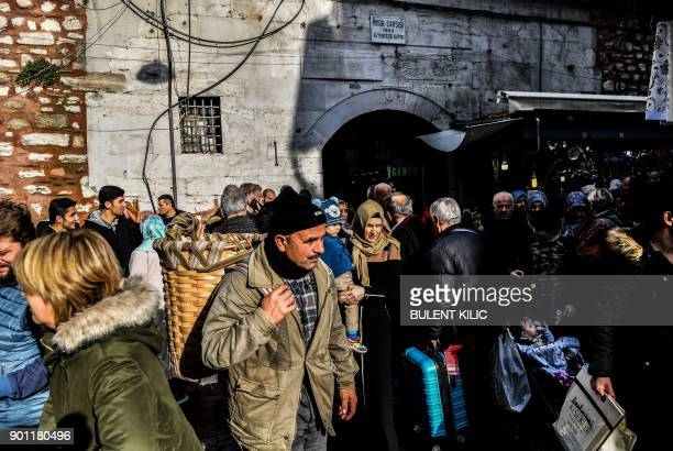 People walk and shop near the Spice Bazaar in the Eminonu quarter of the Fatih district on the European side of Istanbul on January 4 2018 / AFP...