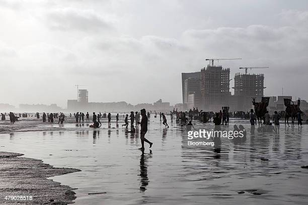 People walk and sit by the sea at Clifton Beach during a heat wave in Karachi Pakistan on Monday June 29 2015 A heat wave where temperatures last...