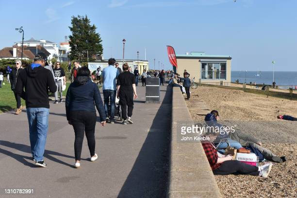 People walk and sit on the beach on a warm sunny Easter Sunday at Westcliff beach on April 04, 2021 in Southend-on-Sea, England. Earlier this week,...