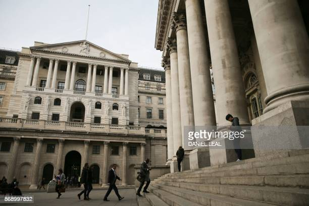 People walk and sit outside the Royal Exchange and The Bank of England in the City of London on November 1 2017 The Bank of England on guard against...