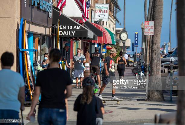 People walk and skateboard on the sidewalk past businesses on a summer day Monday, July 20, 2020 in Newport Beach, CA.