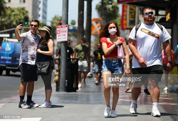 People walk and take photos on Hollywood Boulevard on June 15, 2021 in Los Angeles, California. California, the first state in the U.S. To go into...
