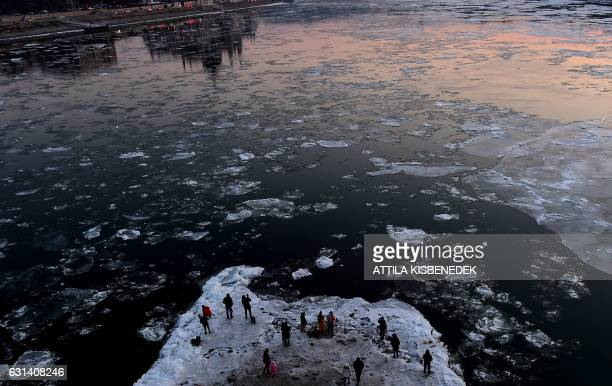 TOPSHOT People walk and take photos under the stonepillar of the Margaret Bridge in Budapest downtown as ice floes float in the water of the River...