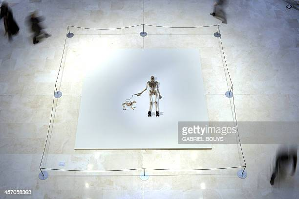 People walk around a piece of art by Gino de Dominicis called Time Error Space representing the skeleton of a man walking with his dog as part of the...