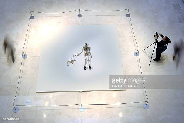 People walk around a piece of art by Gino de Dominicis called Time Error Space representing the skeleton of a man on rollerblades and his dog as part...