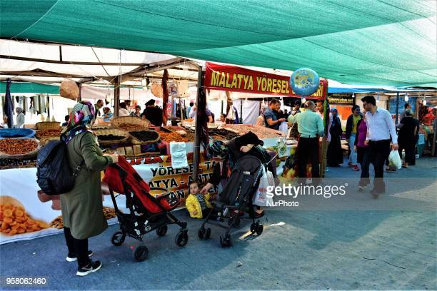 People walk around booths selling local goods in a bazaar ahead of the start of the Muslim holy fasting month of Ramadan in Ankara Turkey on Sunday...