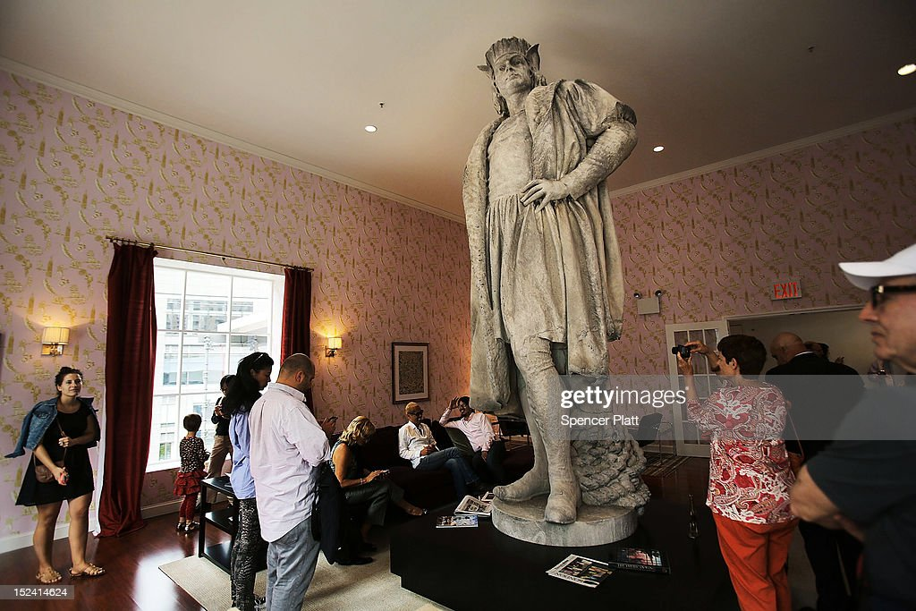 People walk around the 13-foot statue of Christopher Columbus stands in the 810-square-foot 'living room' art installation by Japanese artist Tatzu Nishi on September 20, 2012 in New York City. Viewed as a piece of conceptual art, 'Living Room', sits 70-feet above ground level and is only accessible via a scaffold-encased staircase that has been temporarily built around the Columbus Monument in Columbus Circle. Beginning September 20, up to 25 people at a time can enter the living room and view the 1892 marble figure of the Italian explorer.