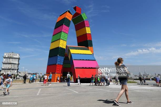 People walk around the art creation 'Catene de conteneurs' by Vincent Ganivet installed for the 500th anniversary of the city of Le Havre on May 27...