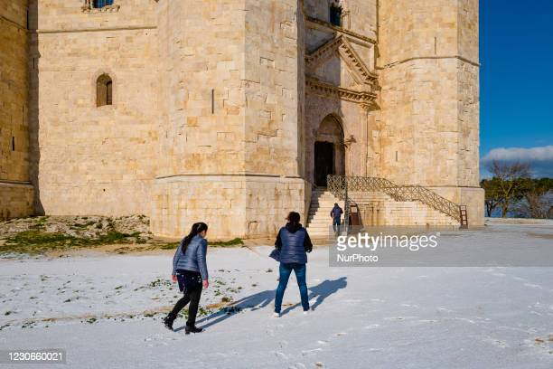 People walk around the Castel del Monte snow-capped by the snowfall of the night on January 18, 2021. The cold wave continues in Puglia, another...