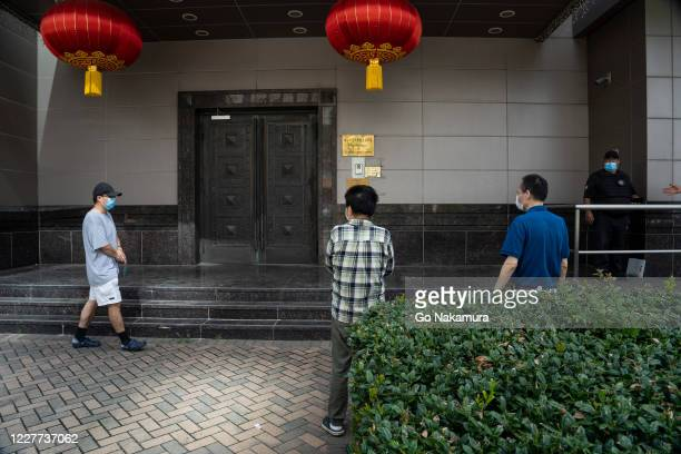 People walk around the Chinese consulate building while trying to gain access after the United States ordered China to close its doors on July 22,...
