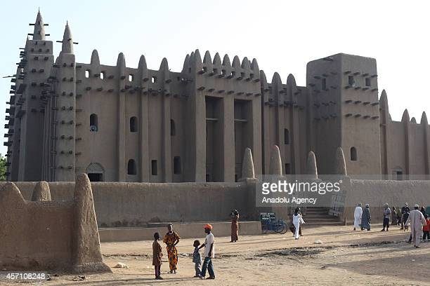People walk around the entrance door of the mud mosque in Djenne Mali on October 6 2014 The Great Mosque of Djenne is the largest mud brick building...