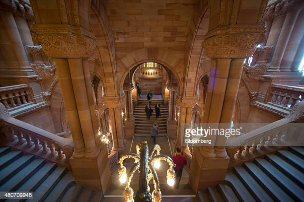 People walk around the Million Dollar Staircase inside the New York State Capitol Building in Albany New York US on Wednesday March 19 2014 Budget...
