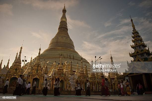 People walk around the Shwedagon Pagoda in Yangon on August 21 2015 Buddhism in Myanmar is predominantly of the Theravada tradition practiced by 89...