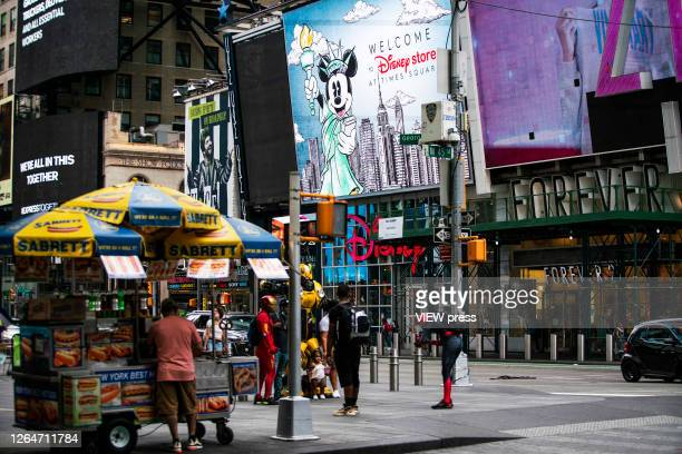 People walk around Times Square on August 8 2020 in New York City With more than four months NYC has closed some of their doors to combat the...