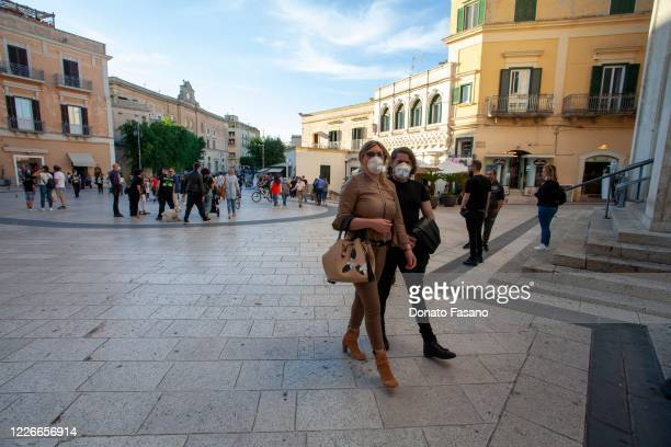 People walk around Via del Corso on May 23 2020 in Matera Italy Restaurants bars cafes hairdressers and other shops have reopened subject to social...