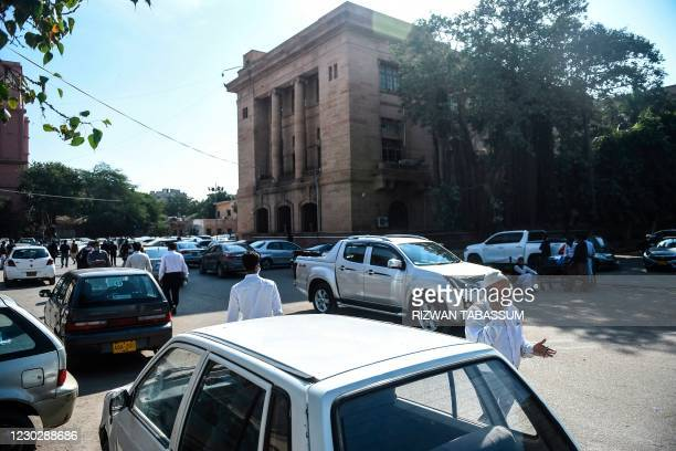 People walk as a high court ordered to release Omar Saeed Sheikh on the murder case of American journalist Daniel Pearl, outside the Sindhhigh court...