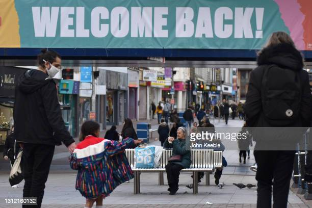 """People walk as an elderly woman sits on a bench on the high street under a bridge with a banner saying """"Welcome Back"""" on April 12, 2021 in..."""